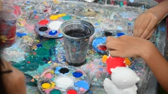 Children painting the plaster doll Stock Footage