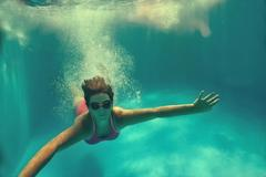 Girl swimming underwater in pool. Stock Photos