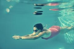 Girl swimming underwater in pool. - stock photo