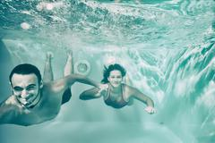 Girl and boy swimming underwater in pool. - stock photo