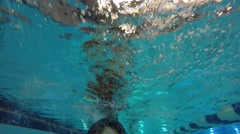 Underwater shot following kid at the swimming pool - stock footage