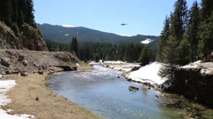 Mountain fast river with helicopter passing by - stock footage