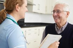 Nurse Discussing Medical Record With Senior Male Patient Stock Photos