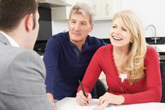 Mature Couple With Financial Advisor Signing Document At Home Stock Photos