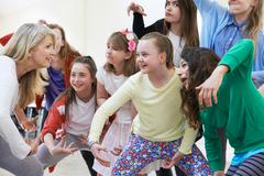 Group Of Children With Teacher Enjoying Drama Class Together Stock Photos