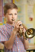 Boy Learning To Play Trumpet In School Music Lesson Kuvituskuvat