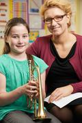 Teacher Helping Pupil To Play Trumpet In Music Lesson Kuvituskuvat