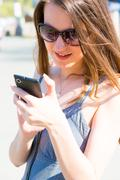 Young woman in sunglasses and summer dress used smartphone or cell phone Stock Photos