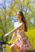 Young woman in short colorful dress with long hair rides a bicycle with  tour Stock Photos