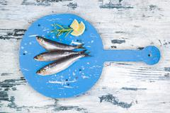 Fresh anchovy fish on white and blue wooden kitchen board. - stock photo