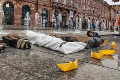 Stock Photo of STRASBOURG, FRANCE - APR 26 2015: Puppets of dead corps and yellow paper boat