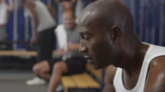 Man in gym locker room rehydrating with water after a workout Stock Footage