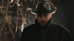 Portrait of terrible maniac with beard at night in hat and coat - stock footage