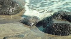 Stones on the sand lapped by the waves of the ocean Stock Footage