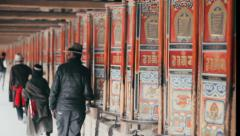 Tibetan Buddhists spin prayer wheels as they perform Kora at Labrang Monastery Stock Footage