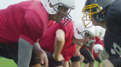 Opposing American football players crouched at line of scrimmage, ready to play - stock footage
