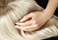 Straight blond wig brushing by a woman - stock photo