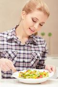 Young woman cooks salad - stock photo