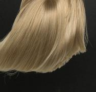 Dense, straight blond wig lying on black background - stock photo