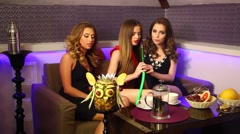 Three young beautiful girls relaxing in the hookah Stock Footage
