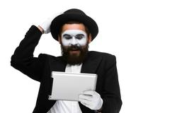 Man with a face mime working on laptop Stock Photos