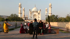 Tourists sitting on a bench with Taj Mahal in background. Stock Footage