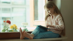Blond little girl using tablet pc. Sitting on the window sill. Child smiling - stock footage