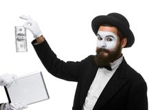 Businessman's hand in the form of mime extract money from tablet PC Stock Photos