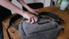 Teenager puts gun in backpack - stock footage