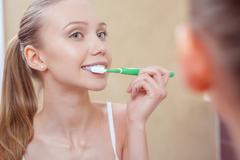 Pretty young woman cleaning her teeth - stock photo