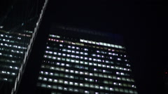 Pan down from London's financial buildings to crowd of people walking at night Stock Footage