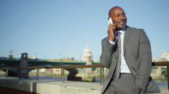 Stock Video Footage of 4K Portrait of cheerful Businessman on mobile phone in the city