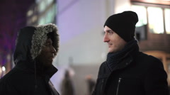 Casual male friends having conversation on city street on a winter evening Stock Footage