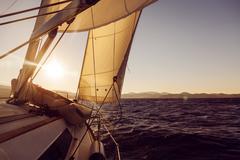 Sailboat crop during the regatta at sunset ocean Stock Photos