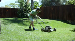 WACKY LOOKING MAN STRUGGLES WITH AN ELECTRIC LAWNMOWER Stock Footage
