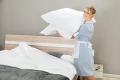 Happy Female Housekeeping Worker With Pillows In Hotel Room Stock Photos