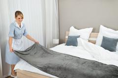 Happy Female Housekeeping Worker Making Bed In Hotel Room Stock Photos