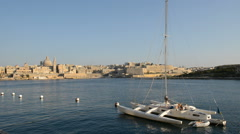The view on Valletta and sail yacht with Ukrainian flag in sunset, Sliema, Malta Stock Footage