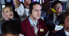4K Portrait of smiling stockbroker in a room full of shouting financial traders - stock footage