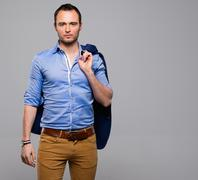 Stock Photo of Sharp dressed fashionist with jacket over shoulder