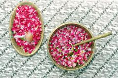 flower petals in water with golden scoop - stock photo