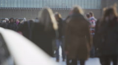 4K Anonymous crowd of city workers & tourists walk on one of London's bridges - stock footage