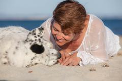 loving dog owner at beach - stock photo