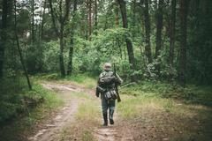 Stock Photo of Unidentified reenactors dressed as German soldiers during march in forest