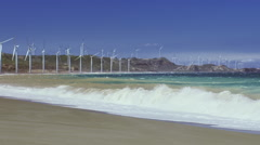 Windy day on ocean shore with big wind mills turbines energy farm on background Stock Footage