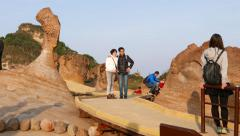 Family taking pictures with Queen's Head hoodoo stone, Yehliu Stock Footage