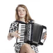 teenage girl sits in studio with accordion - stock photo