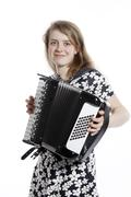 Stock Photo of smiling teenage girl stands in studio with accordion
