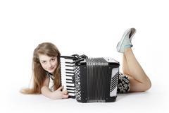 teen girl on the floor in studio with accordion - stock photo