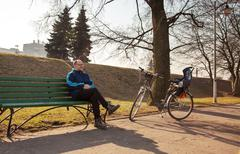 Elderly man sitting on a bench near his bicycle in a city park Kuvituskuvat